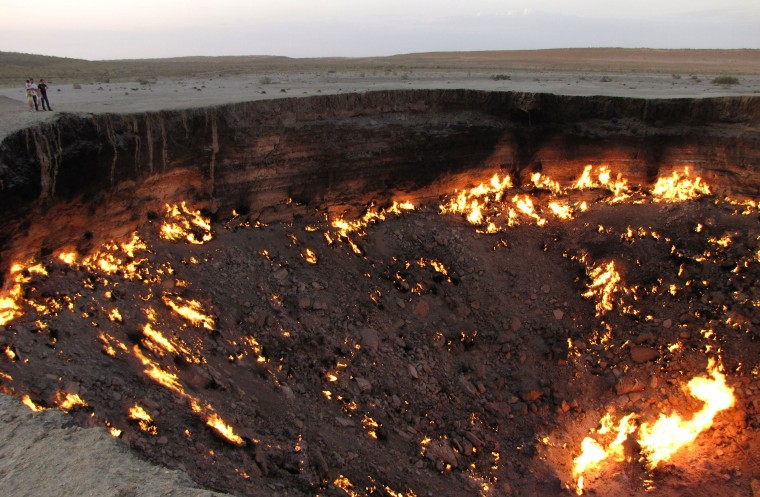 "A picture taken on May 3, 2014, shows people visiting ""The Gateway to Hell,"" a huge burning gas crater in the heart of Turkmenistan's Karakum desert. The fiery pit was the result of a simple miscalculation by Soviet scientists in 1971 after their boring equipment suddenly drilled through into an underground cavern and a deep sinkhole formed. Fearing that the crater would emit poisonous gases, the scientists took the decision to set it alight, thinking that the gas would burn out quickly and this would cause the flames to go out. But the flames have not gone out in more than 40 years, in a potent symbol of the vast gas reserves of Turkmenistan, which are believed to be the fourth largest in the world. (Igor Sasin/AFP/Getty Images)"