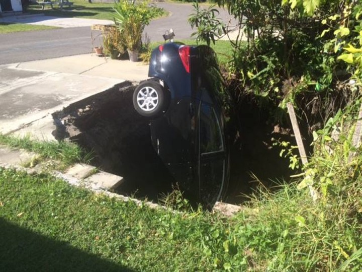 A car is seen in a sinkhole in Holiday, Florida, in this November 10, 2014, handout photo provided by Pasco County. Residents in central Florida on Tuesday monitored the threat of a hole that swallowed a car sitting in a driveway and forced six families to evacuate their homes. (Pasco County/Handout/Reuters)