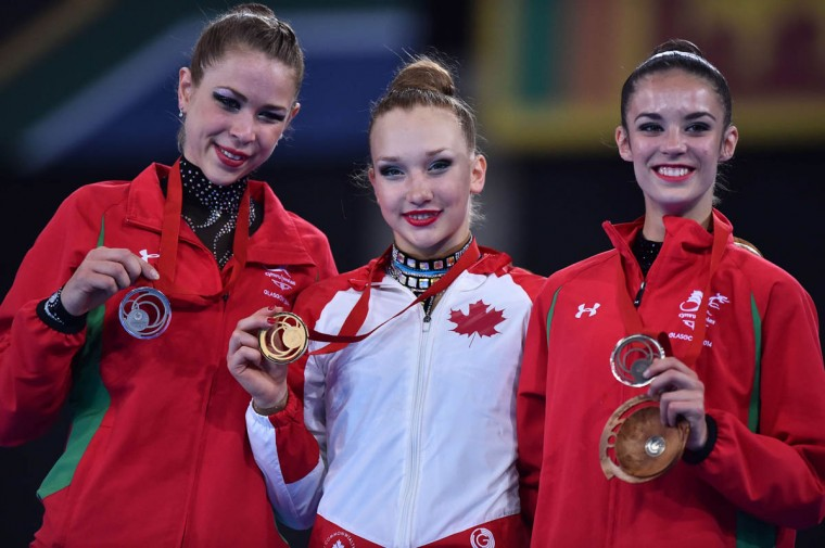 Wales's silver medalist Francesca Jones (Left), Canada's gold medalist Patricia Bezzoubenko (Center) and Wales's Bronze medalist Laura Halford (Right) celebrate with their medals on the podium at the medal ceremony for the Individual All-Around Final of the Rhythmic Gymnastics event at The SSE Hydro venue at the 2014 Commonwealth Games in Glasgow July 25, 2014. (Ben Stansall/Getty Images)