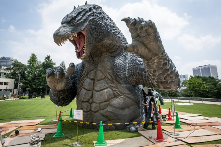 "Crewmember Tetsuo Hayashi airbrushes the final touches to a 6.6 meter replica of the famous Godzilla at Tokyo Midtownin Tokyo, Japan. The ""MIDTOWN Meets GODZILLA"" project is in collaboration with the Japan release of the Hollywood film version of ""Godzilla"" The Godzilla built on the lawns of Tokyo Midtown will host a light show every night complete with mist, audio and fire rays. (Chris McGrath/Getty Images)"