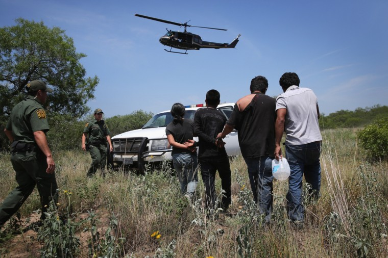 U.S. Customs and Border Protection agents take undocumented immigrants into custody on July 22, 2014 near Falfurrias, Texas. Thousands of immigrants, many of them minors, have crossed illegally into the United States this year, causing a humanitarian crisis on the U.S.-Mexico border. Texas Governor Rick Perry announced that he will send 1,000 National Guard troops to help stem the flow. (Photo by John Moore/Getty Images)