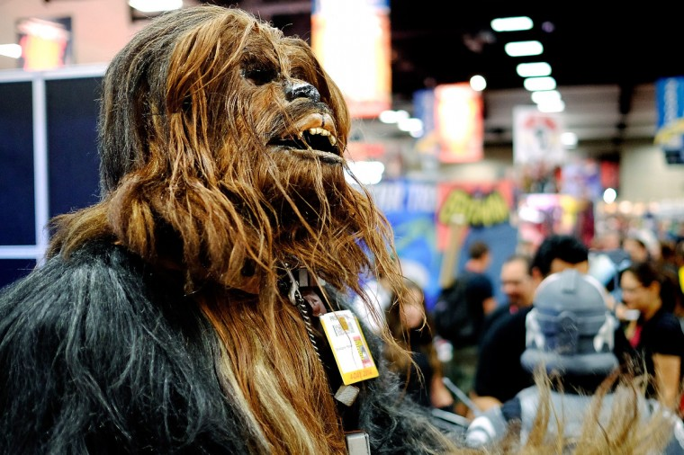 Christopher Petrone, of San Diego, CA, towering over attendees in his handmade, to-scale Chewbacca costume, gives a roar to fans during the 45th annual San Diego Comic-Con on July 24, 2014 in San Diego, California. An estimated 130,000 attendees are expected at this year's convention, which will celebrate the 75th anniversary of both Marvel Comics and the first Batman comic book. (T.J. Kirkpatrick/Getty Images)
