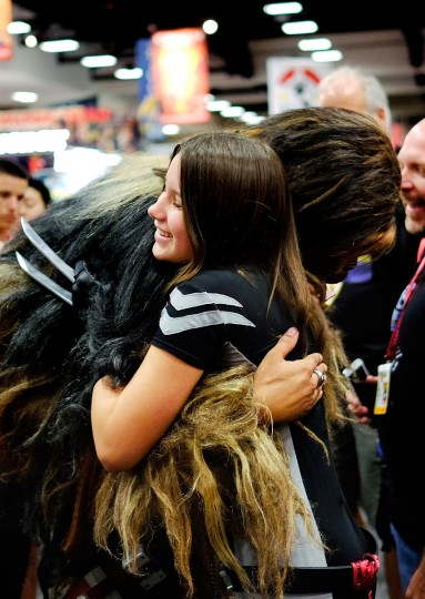 Christopher Petrone, of San Diego, CA, towering over attendees in his handmade, to-scale Chewbacca costume, bends down to hug a fan during the 45th annual San Diego Comic-Con on July 24, 2014 in San Diego, California. An estimated 130,000 attendees are expected at this year's convention, which will celebrate the 75th anniversary of both Marvel Comics and the first Batman comic book. (T.J. Kirkpatrick/Getty Images)