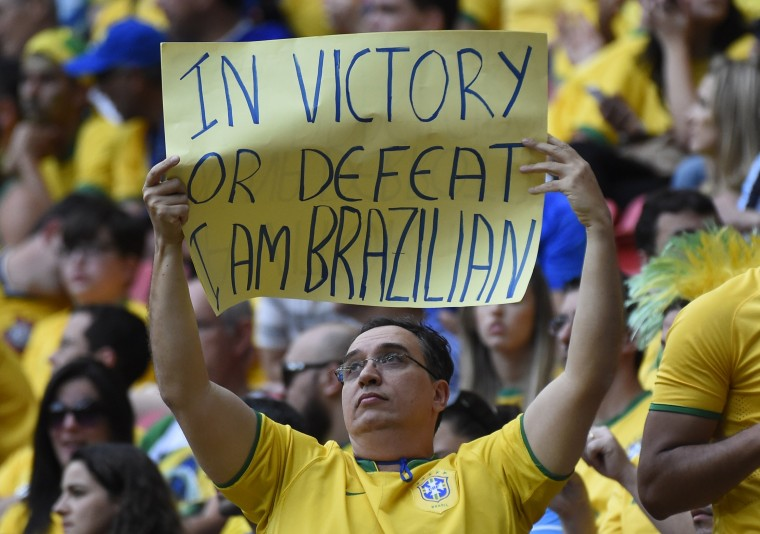 A fan holds up a placard prior to the third place play-off football match between Brazil and Netherlands during the 2014 FIFA World Cup at the National Stadium in Brasilia on July 12, 2014. (Odd Andersen/AFP/Getty Images)