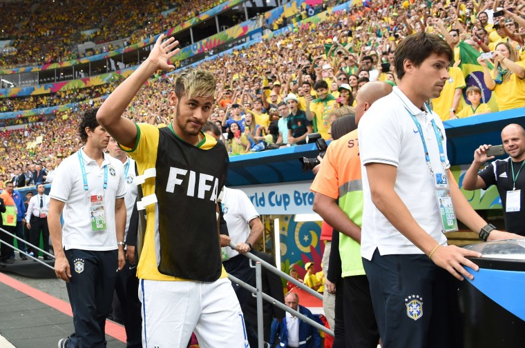 Brazil's injured forward Neymar (C) waves at supporters as he walks towards the bench during the third place play-off football match between Brazil and Netherlands during the 2014 FIFA World Cup at the National Stadium in Brasilia on July 12, 2014. (Vanderlei Almeida/AFP/Getty Images)