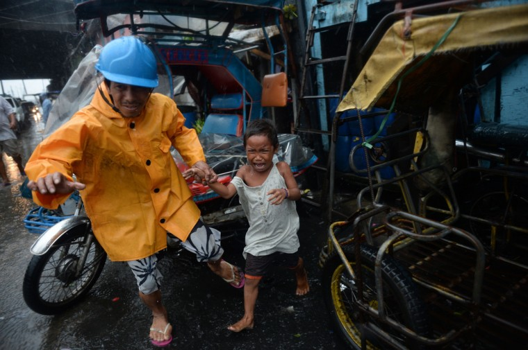 A village official leads a child as he is evacuated from their house at an informal settlers' area as Typhoon Rammasun barrels across Manila on. Typhoon Rammasun shut down the Philippine capital on July 16 as authorities said the first major storm of the country's brutal rainy season claimed at least one life and forced hundreds of thousands to evacuate. (Ted Aljibe/Getty Images)