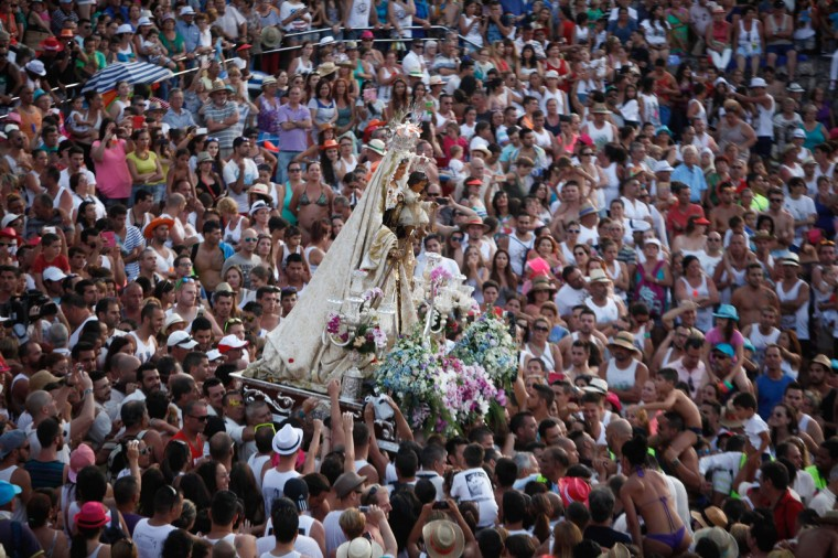 Penitents carry a statue of the Virgen del Carmen, the patron saint of fishermen, as thousands of people attend the procession at the Puerto de la Cruz on the Spanish Canary island of Tenerife. Every year, local residents of the resort carry the statue of the Virgin from its chapel to a small beach in the fishing habor. Once at the beach, the fishermen put the statue on board a decorated boat and the statue sails along the coast. (Desiree Martin/Getty Images)
