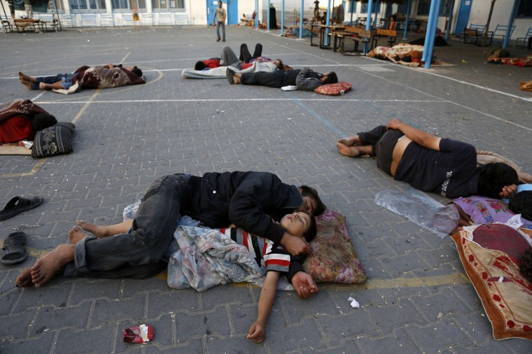 Palestinians sleep at the yard of a UN school in the northern Gaza Strip town of Beit Lahiya early on, after evacuating their houses near the border with Israel. The Israeli army has warned some 100,000 Palestinians in the eastern Gaza Strip to evacuate their homes, military sources said. Since July 8, militants have fired nearly 1,000 rockets and mortars into the Jewish state, and Israel has carried out around 1,500 strikes against targets inside Gaza. (Mohammed Abed/Getty Images)