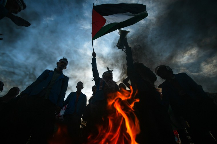 Indonesian demonstrators raise the Palestinian flag while they burn an Israeli and US flag during a demonstration in Banda Aceh, on Sumatra island on, condemning Israel's offensive in Gaza. Israel urged 100,000 Gazans to flee their homes on July 16, but the warning was largely ignored despite an intensification of the military's nine-day campaign after Hamas snubbed a ceasefire effort. Indonesia with a population of about 220 million is the world's most populous Muslim-majority country. (Chaideer Mahyuddin/Getty Images)
