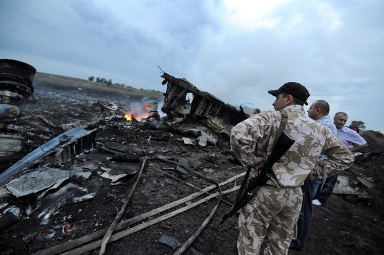 People stand next to the wreckages of the Malaysian airliner carrying 295 people from Amsterdam to Kuala Lumpur after it crashed, near the town of Shaktarsk, in rebel-held east Ukraine, on July 17, 2014. Pro-Russian rebels fighting central Kiev authorities claimed on Thursday that the Malaysian airline that crashed in Ukraine had been shot down by a Ukrainian jet. (Dominique Faget/Getty Images)