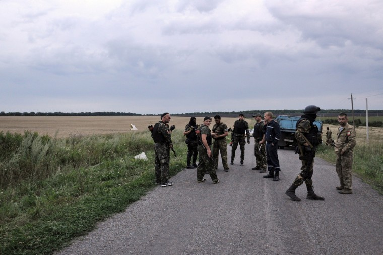 People wearing military fatigues, stand on a road, on July 17, 2014 at the site of the crash of a Malaysian airliner carrying 295 people from Amsterdam to Kuala Lumpur, near the town of Shaktarsk, in rebel-held east Ukraine. Pro-Russian rebels fighting central Kiev authorities claimed on Thursday that the Malaysian airline that crashed in Ukraine had been shot down by a Ukrainian jet. The head of Ukraine's air traffic control agency said Thursday that the crew of the Malaysia Airlines jet that crashed in the separatist east had reported no problems during flight. (Dominique Faget/Getty Images)