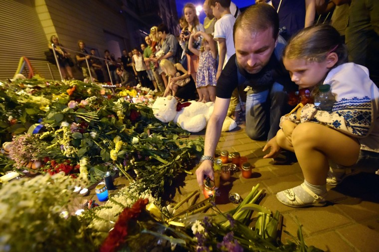 "A man lights a candle in front of the Embassy of the Netherlands in Kiev on July 17, 2014, to commemorate passengers of Malaysian Airlines flight MH17 carrying 295 people from Amsterdam to Kuala Lumpur which crashed in eastern Ukraine. Ukrainian President Petro Poroshenko said on July 17 that the Malaysia Airlines jet that crashed over rebel-held eastern Ukraine may have been shot down."" Ukraine's government and pro-Russian insurgents traded blame for the disaster, with comments attributed to a rebel commander suggesting his men may have downed Malaysia Airlines flight MH17 by mistake, believing it was a Ukrainian army transport plane. (Sergei Supinsky/Getty Images)"
