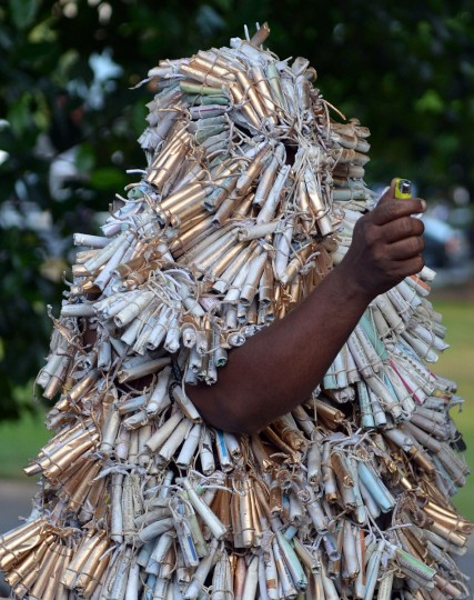 A Sri Lankan activist, who wrapped himself with fire crackers, holds a lighter as he walks in Colombo on July 23, 2014 to symbolically demonstrate against people burned during Anti-Tamil riots on the island thirty-one years ago. Official accounts placed the death toll at 400 while human rights activists put the toll at thousands. (Ishara S. Kodikara/AFP/Getty Images)