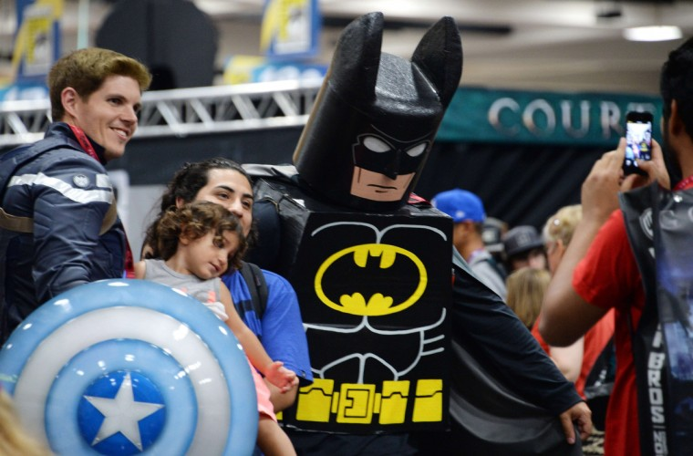 A mother and child pose for a photo with costumed attendees on the first day of the 45th annual San Diego Comic-Con, in San Diego California July 24, 2014. The four-day pop culture extravaganza celebrates film, TV, video games, comic books, costumes and other popular arts. More than 150,000 fans are expected to attend the sold-out event. (Robyn Beck/Getty Images)