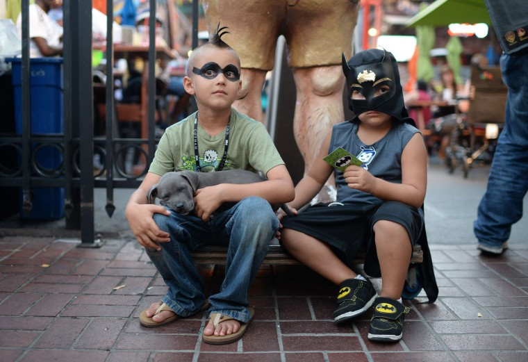 Seven-year-old Ashton Ritz (L) and four-year-old Dezmen Olivas sit together on the first day of the 45th annual Comic-Con, in San Diego, California July 24, 2014. The four-day pop culture extravaganza celebrates film, TV, video games, comic books, costumes and other popular arts. More than 150,000 fans are expected to attend the sold-out event. (Robyn Beck/AFP/Getty Images)