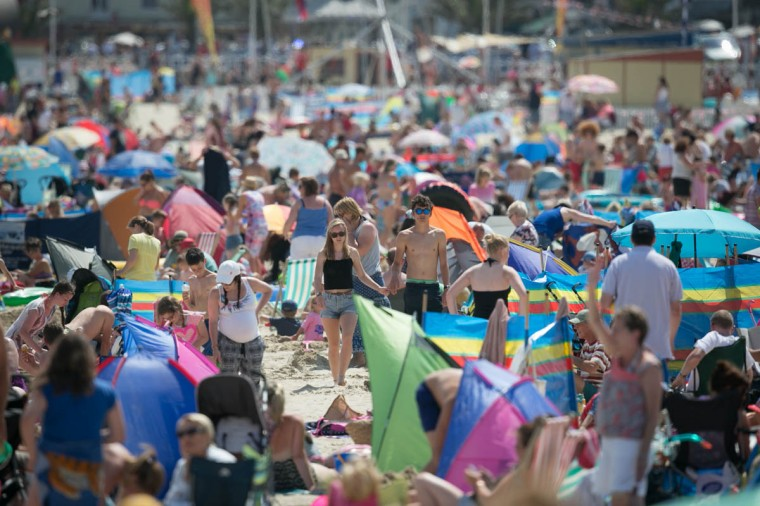 Visitors to Weymouth enjoy the warm weather on the seafront on July 30, 2014 in Weymouth, England. Figures released by the Met Office show that this July is likely to go down as one of the warmest and sunniest on record. However the arrival of August will also see the return of more unsettled weather with the potential for heavy rain at the weekend. (Matt Cardy/Getty Images)