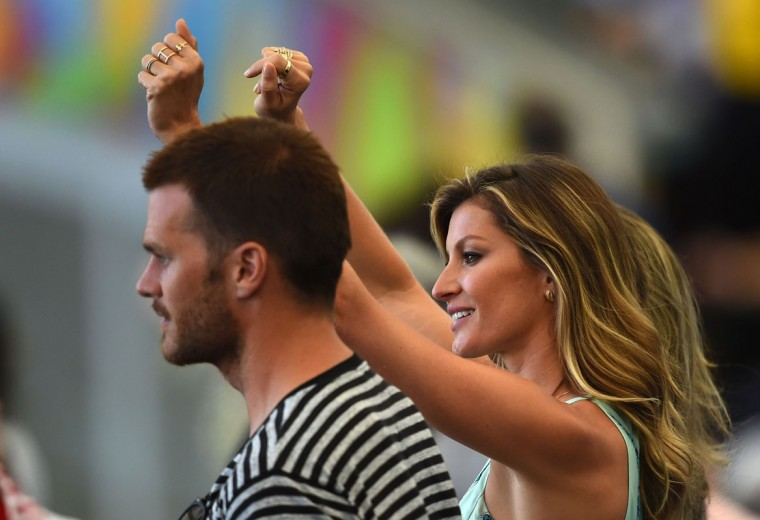 Brazilian model Gisele Bundchen (R) gestures alongside US American football player Tom Brady during a closing ceremony ahead of the final football match between Germany and Argentina for the FIFA World Cup at The Maracana Stadium in Rio de Janeiro on July 13, 2014. (Christophe Simon/AFP/Getty Images)