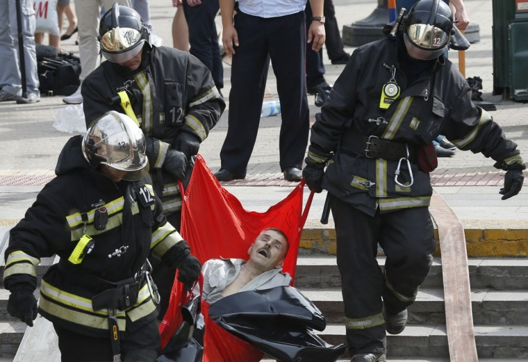 Rescuers carry a passenger injured as several subway cars derailed in Moscow, on July 15, 2014. At least twelve people died and scores were taken to hospital today after a train derailed in the Moscow metro in a tunnel between Park Pobedy and Slavyansky Bulvar stations, in the west of Moscow, city authorities said. (AFP PHOTO/ITAR-TASS/Getty Imagse/Mikhail Japaridze)