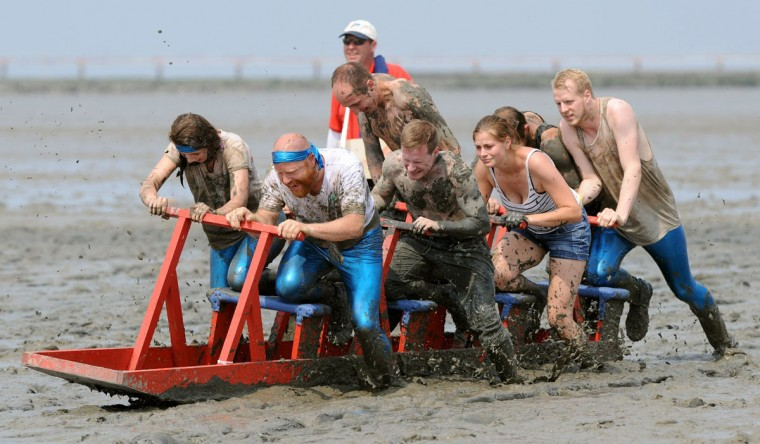 "Participants of the mudflat sledge championships push their sledge through the wadden sea on July 20, 2014 in Upleward, northern Germany. The competition was titled ""Dirty sports for a clean job"" and was a charity event in favor of a regional association fighting against cancer. (Ingo Wagner/AFP/Getty Images)"