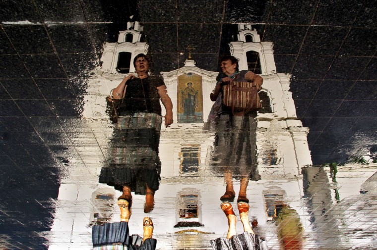 Two women walking in front of Svyato-Dukhov (Holy Spirit ) Orthodox cathedral are reflected in the wet tablets of a roadway in the Belarus capital Minsk, on July 20, 2014. (AFP PHOTO/Getty Images/ Sergei Gapon)