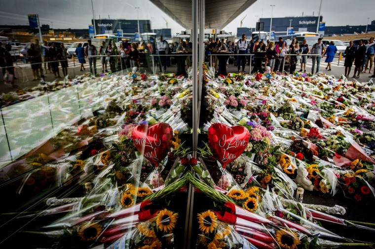 People look at the flowers left in remembrance for the victims of the MH17 plane crash at Schiphol Airport, near Amsterdam, on July 21, A Malaysia Airlines Boeing 777 flight MH17 with more than 280 passengers, including 193 Dutch passengers on board crashed in eastern Ukraine on 17 July. A chorus of Kremlin-friendly media declared today that the truth about what happened to the Malaysian jet would likely never be found out, accusing the West of heaping the blame on Russia. (AFP PHOTO/Getty Images/Robin van Lonkhuijsen)