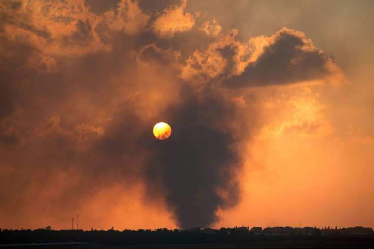 A picture taken on July 20, 2014, from Israel at the southern border with the Gaza strip shows smoke billowing from behind a hill following an Israeli air strike on Gaza City. The number of Palestinians killed in Israeli attacks in the Gaza Strip on July 20 was at least 100. It was the bloodiest single day in the battered enclave in five years, taking the Palestinian toll on the 13th day of Israel's Gaza offensive to 438. (AFP PHOTO/Getty Images/Menahem Kahana)