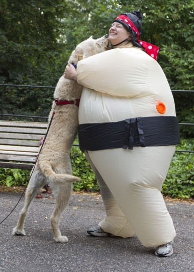 A dog jumps up onto a participant in an inflated suit before taking part in The Sumo Run in Battersea Park, London, on July 27, 2014. The Sumo Run is an annual 5km charity fun run around the park in inflatable sumo suits. (Justin Tallis/AFP/Getty Images)