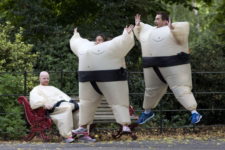 Participant wearing inflated suits jump before the start of The Sumo Run in Battersea Park, London, on July 27, 2014. The Sumo Run is an annual 5km charity fun run around the park in inflatable sumo suits. (Justin Tallis/AFP/Getty Images)