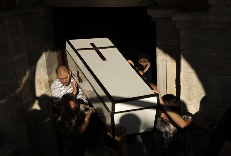Palestinians carry the coffin of Jalila Ayad, a Christian woman whose body was found under the rubble of her home after an Israeli air strike in Gaza City during her funeral on July 27, 2014. The Islamist Hamas movement continued firing rockets at Israel, despite claims it had accepted a UN request for a 24-hour extension of a humanitarian truce in war-torn Gaza. (Mohammed Abed/AFP/Getty Images)