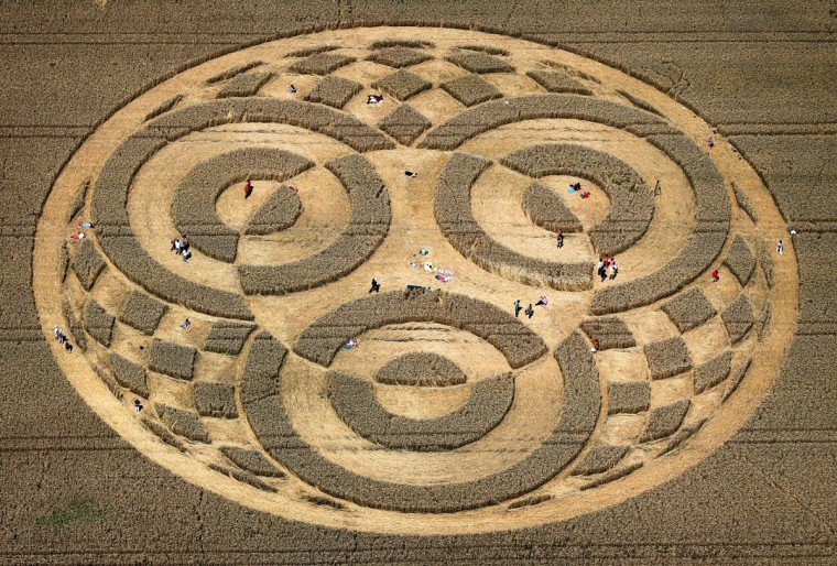 People walk through crop circles shaped into a cornfield near Raisting, southern Germany, on July 28, 2014. According to media reports, a balloonist had discovered the circle some days ago. Since then, hundreds of people came to the field to watch it, however it is unclear who did create the pattern. (AFP PHOTO/ DPA/Karl-Josef Hildenbrand)