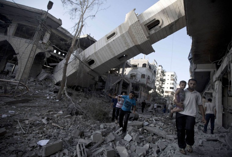 """Palestinians walk past the collapsed minaret of a destroyed mosque in Gaza City, on July 30 2014 after it was hit in an overnight Israeli strike. Overnight Israeli bombardments killed """"dozens"""" of Palestinians in Gaza, including at least 16 at a UN school, medics said, on day 23 of the Israel-Hamas conflict. (Mahmud Hams/Getty Images)"""