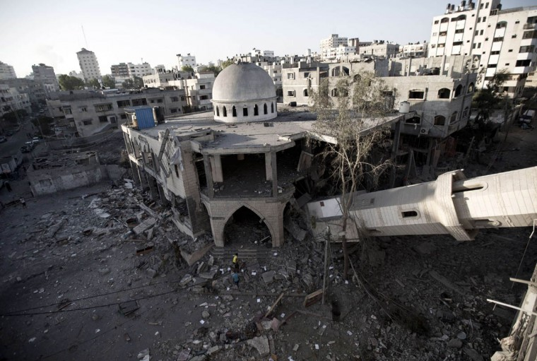 """A general view shows the collapsed minaret of a destroyed mosque in Gaza City, on July 30 2014 after it was hit in an overnight Israeli strike. Israeli bombardments killed """"dozens"""" of Palestinians in Gaza, including at least 16 at a UN school, medics said, on day 23 of the Israel-Hamas conflict. (Mahmud Hams/Getty Images)"""