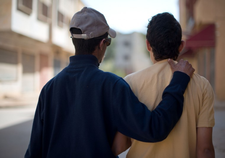 "From left, Driss Hamouti, 21, puts his arm around his best friend, Zahir Bouten, 21, both of Tifelt, Morocco, as they take a walk around Tifelt. ""If he has somewhere to go, he will go. He doesn't care,"" said Driss' sister, Wafae Hamouti, (not pictured). Rachel Woolf/Baltimore Sun"