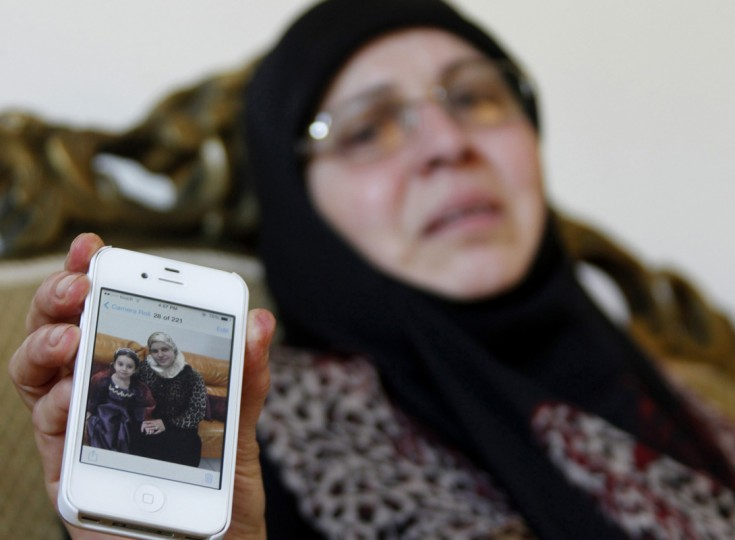 The sister-in-law of Lebanese passenger Randa Daher reacts as she holds her mobile phone displaying a picture of Randa and one of her children at her home in the southern Lebanese village of Srifa July 24, 2014. According to local media, Randa and her children were on board Air Algerie flight AH 5017, which an Algerian aviation official said crashed on Thursday en route from Ouagadougou in Burkina Faso to Algiers with 110 passengers on board. (Ali Hashisho/Reuters)