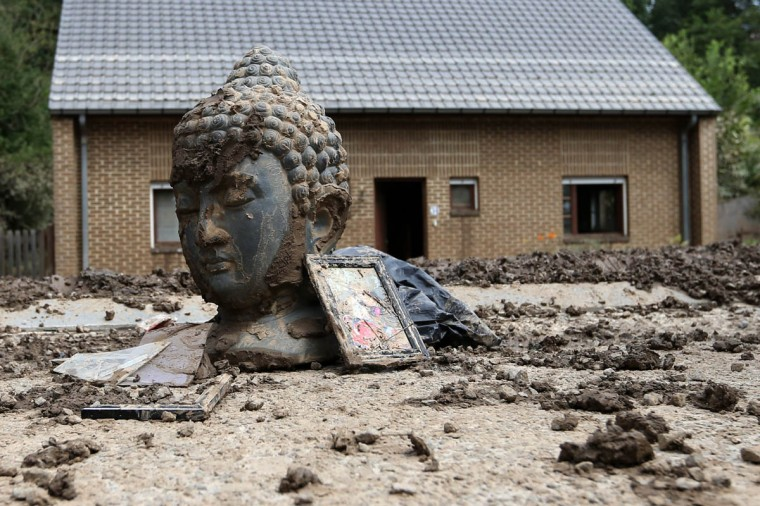 A statue of Buddha and storm debris are covered with mud outside a flooded house after heavy rains hit the town of Ittre July 30, 2014. (Francois Lenoir/Reuters photo)