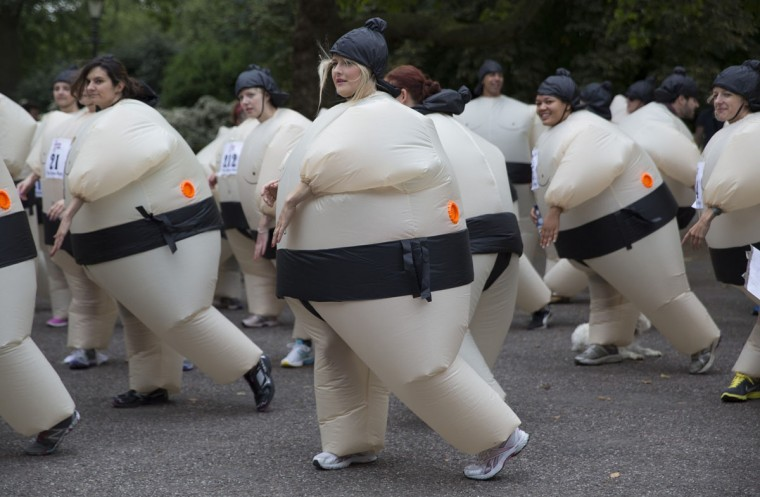 Participants warm up before The Sumo Run in Battersea Park, London July 27, 2014. The runners, wearing inflatable costumes, take part in the 5km run with the aim of raising money for a charity to help educate children in Africa. (Neil Hall/Reuters)