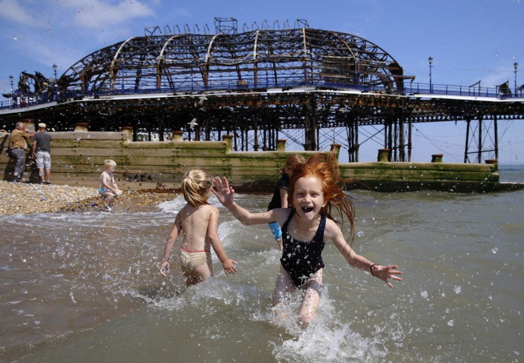 Seven year old Lily Blackburn plays with friends in the sea near the burnt remains of a section of Eastbourne pier, in Eastbourne, southern England July 31, 2014. A Victorian-era seaside pier at Eastbourne on Britain's south coast was badly damaged when fire broke out in an amusement arcade on Wednesday. Flames could be seen leaping from the roof of the two-storey structure as a large plume of smoke rose above the town. REUTERS/Luke MacGregor
