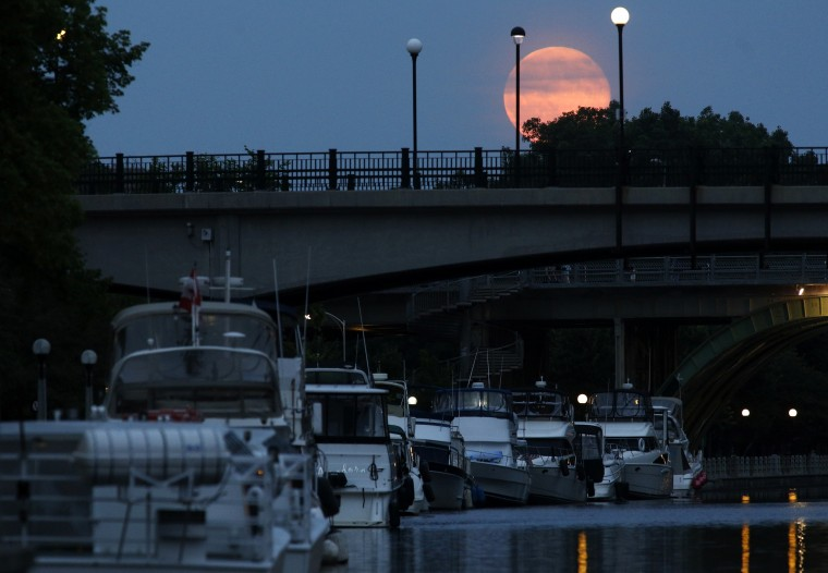 A Supermoon is seen over the Rideau Canal in Ottawa July 12, 2014. Occurring when a full moon or new moon coincides with the closest approach the moon makes to the Earth, the Supermoon results in a larger-than-usual appearance of the lunar disk. REUTERS/Blair Gable