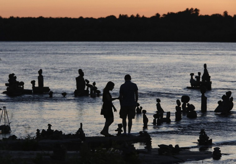 A couple look at stone sculptures at the Remic Rapids in the Ottawa River during sunset at Ottawa July 23, 2014. (Chris Wattie/Reuters)
