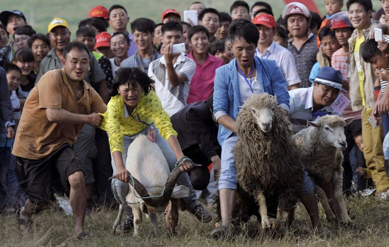 People look on as participants ride goats and sheep during a race to celebrate a local festival in Fengshan town, Guizhou province. (China Daily/Reuters)