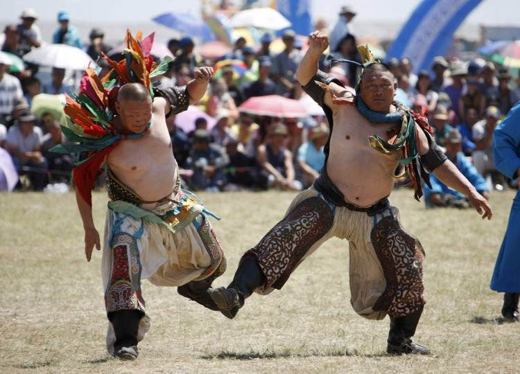 Wrestlers dance during the traditional Nadam Fair in Xilin Gol League, in China's Inner Mongolia Autonomous Region, July 30, 2014. Around 768 people, including children and women wrestlers, participated in the event, according to local media. Picture taken July 30, 2014. REUTERS/Jacky Chen