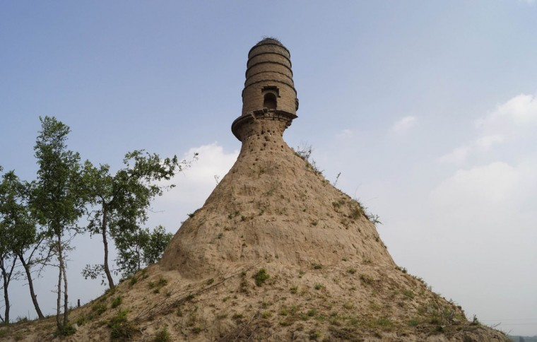 An ancient tower is seen balancing on the top of a dirt hill, with its base slightly eroded, along a grassland in Qixian county, Shanxi province July 19, 2014. Local authorities said they were looking into way to protect and remedy the tower after pictures, taken by a relic preservation enthusiast, were posted on the Internet, local media reported. Picture taken July 19, 2014. (REUTERS/Stringer)