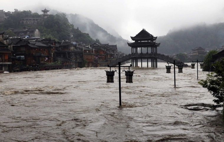 Street lamps are seen among floodwaters next to partially submerged buildings by an over flowing river at the ancient town as heavy rainfall hits Fenghuang county, Hunan province July 15, 2014. More than 50,000 locals and tourists were evacuated since Monday night as record downpours hit Fenghuang county of central China's Hunan province, Xinhua News Agency reported. (REUTERS/China Daily)