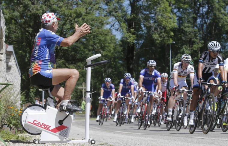A cycling fan on a home trainer cheers as the pack of riders cycles on its way during the 187.5-km 11th stage of the Tour de France cycling race between Besancon and Oyonnax, July 16, 2014. (Christian Hartmann/Reuters)
