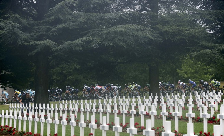 The pack of riders cycles past the cemetery outside of the WWI Douaumont ossuary near Verdun during the 234.5 km seventh stage of the Tour de France cycling race from Epernay to Nancy July 11, 2014. (Jean-Paul Pelissier/Reuters)