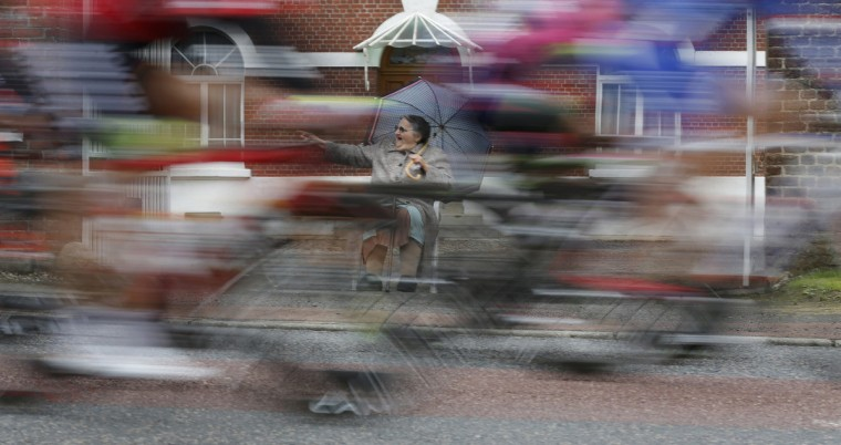 An elderly woman cheers as the pack of riders cycles on its way during the 194 km sixth stage of the Tour de France cycling race from Arras to Reims July 10, 2014. Picture taken with low shutter speed. (Christian Hartmann/Reuters)