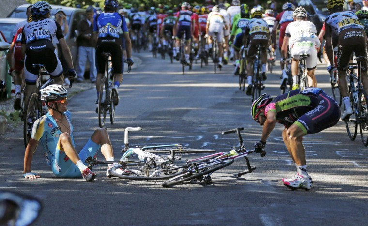 Astana team rider Michele Scarponi of Italy and Lampre-Merida team rider Jose Rodolfo Serpa of Colombia recover after crashing during the 187.5-km 11th stage of the Tour de France cycling race between Besancon and Oyonnax, July 16, 2014. (Jean-Paul Pelissier/Reuters)