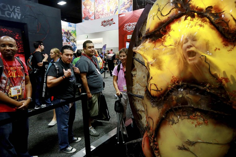"""Jill Olsen (R) has her picture taken inside a giant cocoon, from the """"Falling Skies"""" TV series, during the 2014 Comic-Con International Convention in San Diego, California July 24, 2014. (Sandy Huffaker/Reuters)"""