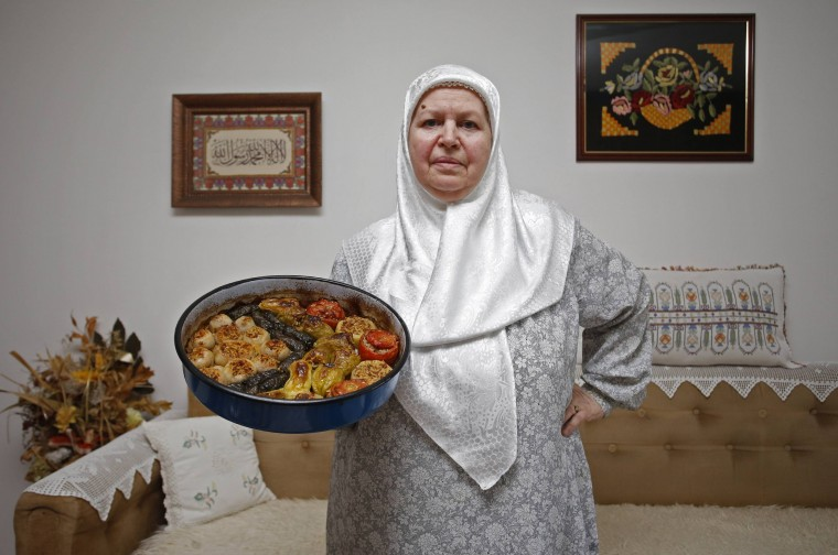 Mevlida Mrgic, 66, poses for a photograph as she holds a plate of dolma, a traditional dish of stuffed vegetables, in the central Bosnian town of Zenica July 13, 2014. During Ramadan, the ninth and holiest month in the Islamic calendar, Muslims refrain from eating and drinking during daylight hours. Reuters photographers took a series of portraits of Muslims observing Ramadan in different countries around the world, and asked them what food they liked to eat when breaking their daily fast. Eid-al-Fitr, marking the end of Ramadan, will be celebrated at the beginning of next week. Picture taken July 13, 2014. (Dado Ruvic/Reuters)