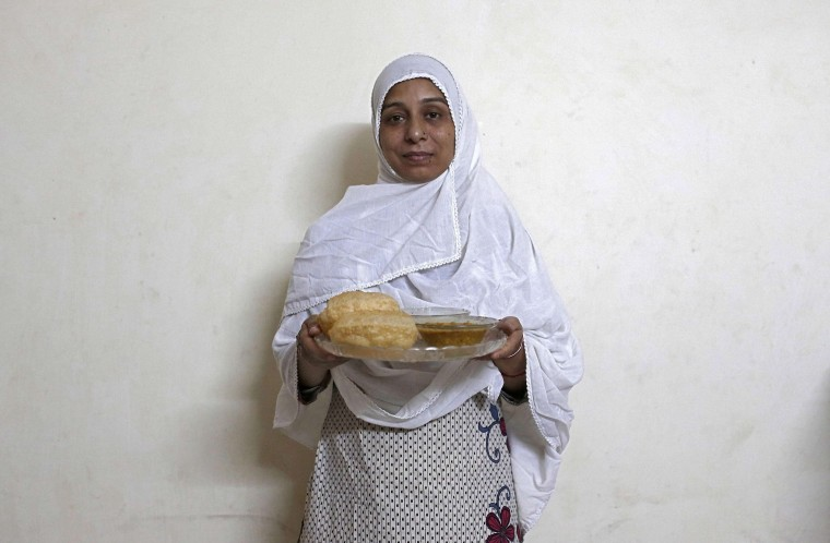 Sara Naqvi, 36, holds a plate of her favourite Iftar meal, puri-cholea, deep fried bread and spicy chickpeas, as she waits to break her fast in New Delhi, July 15, 2014. During Ramadan, the ninth and holiest month in the Islamic calendar, Muslims refrain from eating and drinking during daylight hours. Reuters photographers took a series of portraits of Muslims observing Ramadan in different countries around the world, and asked them what food they liked to eat when breaking their daytime fast. Eid-al-Fitr, marking the end of Ramadan, will be celebrated at the beginning of next week. Picture taken July 15, 2014. (Adnan Abidi/Reuters)